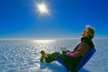 A polar explorer relaxes on a bare ice glacier in Queen Maud Land.