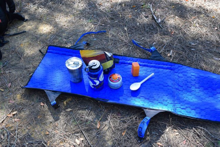 Image of the Crazy Creek HEX 2.0 PowerLounger with a portable stove and a bog of food on top