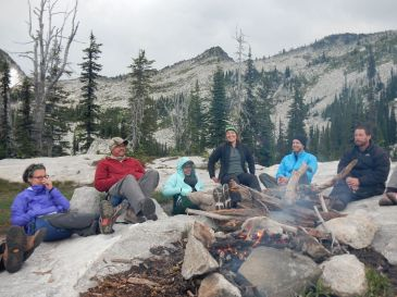 6 People sitting around a campfire with mountains in the background