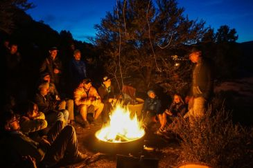 Picture with a campfire and people sitting and standing around the fire