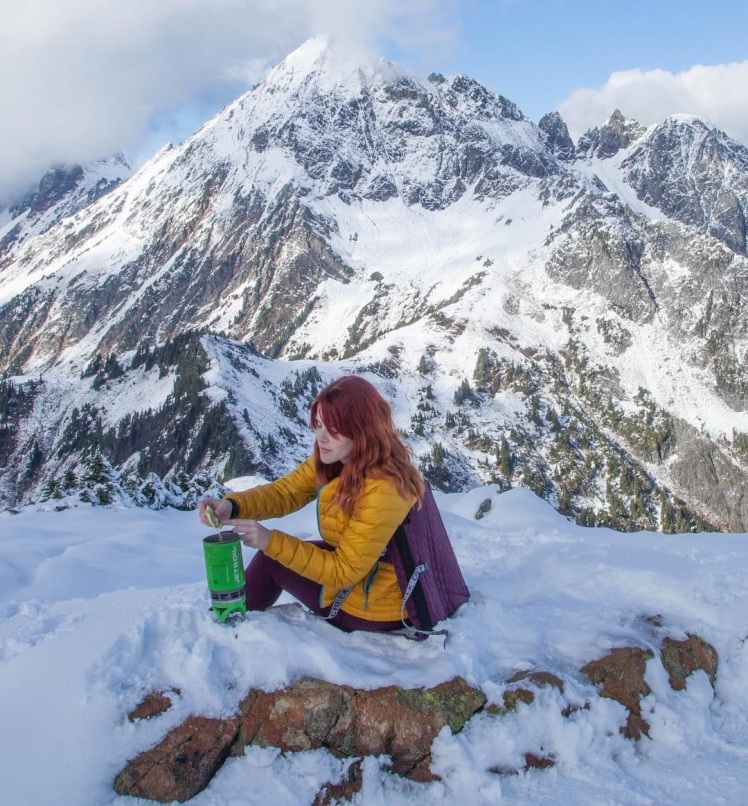 Lady sitting in a Crazy Creek Chair in the snow making something hot to eat