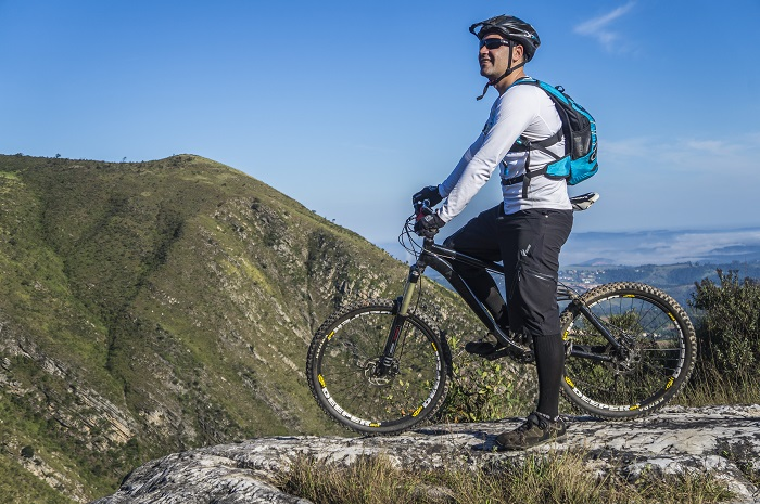 Man on a bike on top of a mountain with a backpack on