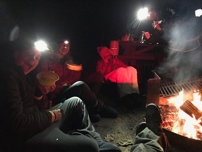 Group of people sitting around a campfire with headlamps on