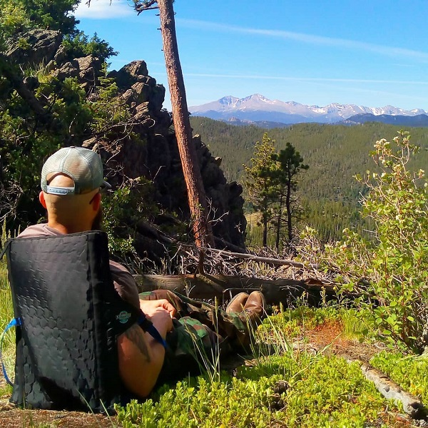 Man sitting in a Crazy Creek chair looking out at Longs Peak from a mountain top