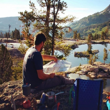 Man reading a map by the water with a Crazy Creek chair in the picture