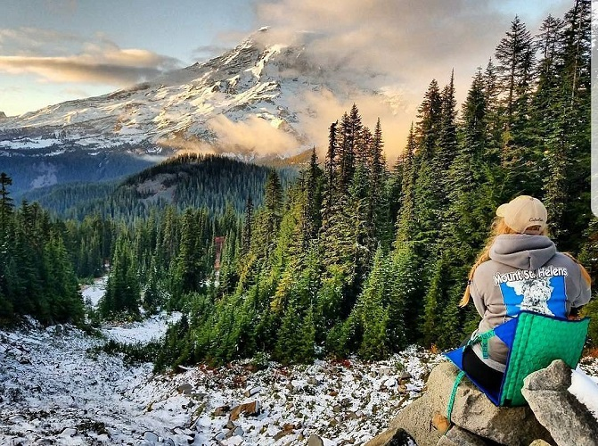 Women sitting in a Crazy Creek chair overlooking a snow capped mountain