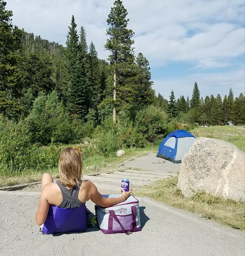 Car camping with a tent and person sitting in a Crazy Creek chair