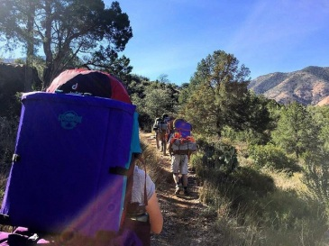 Group backpacking on a trail with crazy creek chairs on the outside of their bags.
