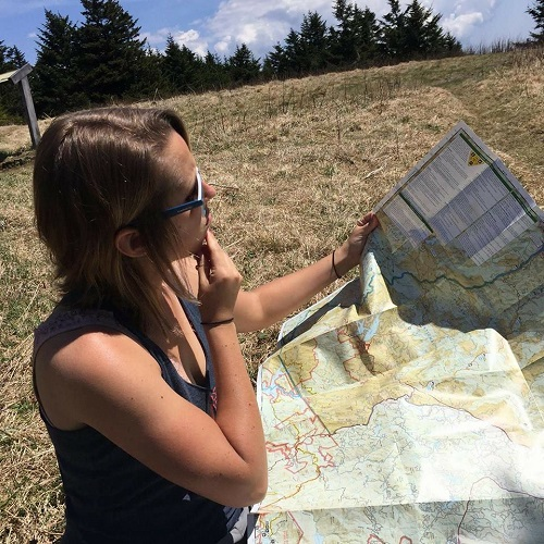 Person looking at a map outdoors on a hike
